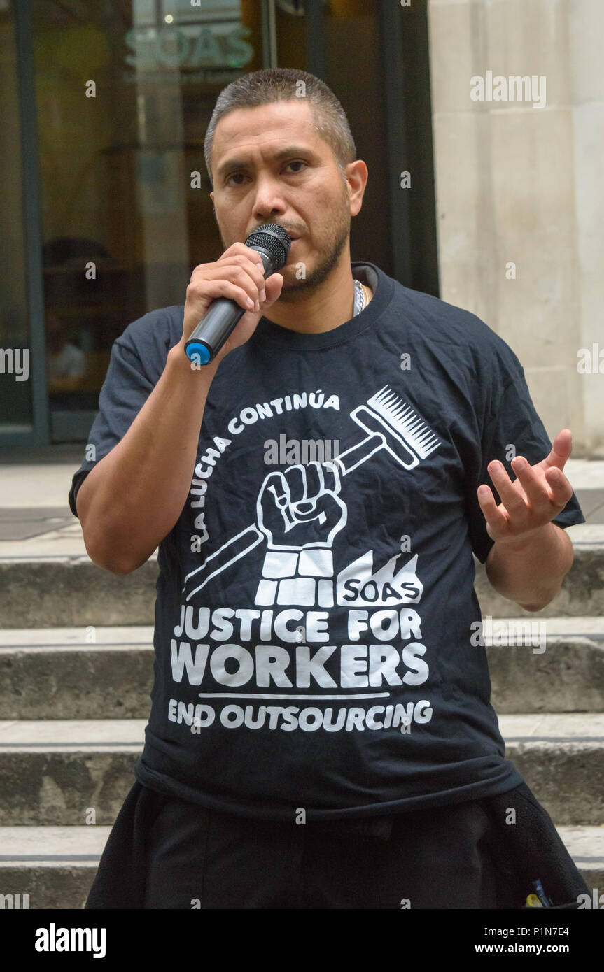 London, UK. 12th June 2018. Lenin, one of the cleaners speaks in front of the 'Justice For Cleaners' banner at the rally at the SOAS steps remembing the SOAS cleaners called by SOAS to an 'emergency meeting' at 6:30am on 12th June 2009 after cleaners had campaigned to get the London Living Wage. A few minutes after the start of the meeting, agents of the UK Border Agency rushed in, handcuffed all the cleaners and held them for questioning. Nine were then deported. Credit: Peter Marshall/Alamy Live News - Stock Image