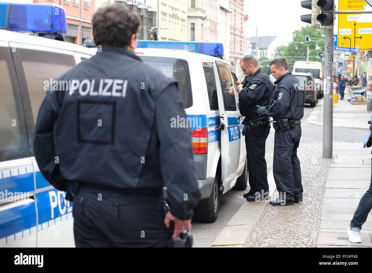 13 June 2018, Leipzig, Germany: Officers of the federal police accompany stand in front of a residential building in the city district Plagwitz. A police deployment took place due to sham marriage suspicions. Photo: Sebastian Willnow/dpa-Zentralbild/dpa - Stock Image
