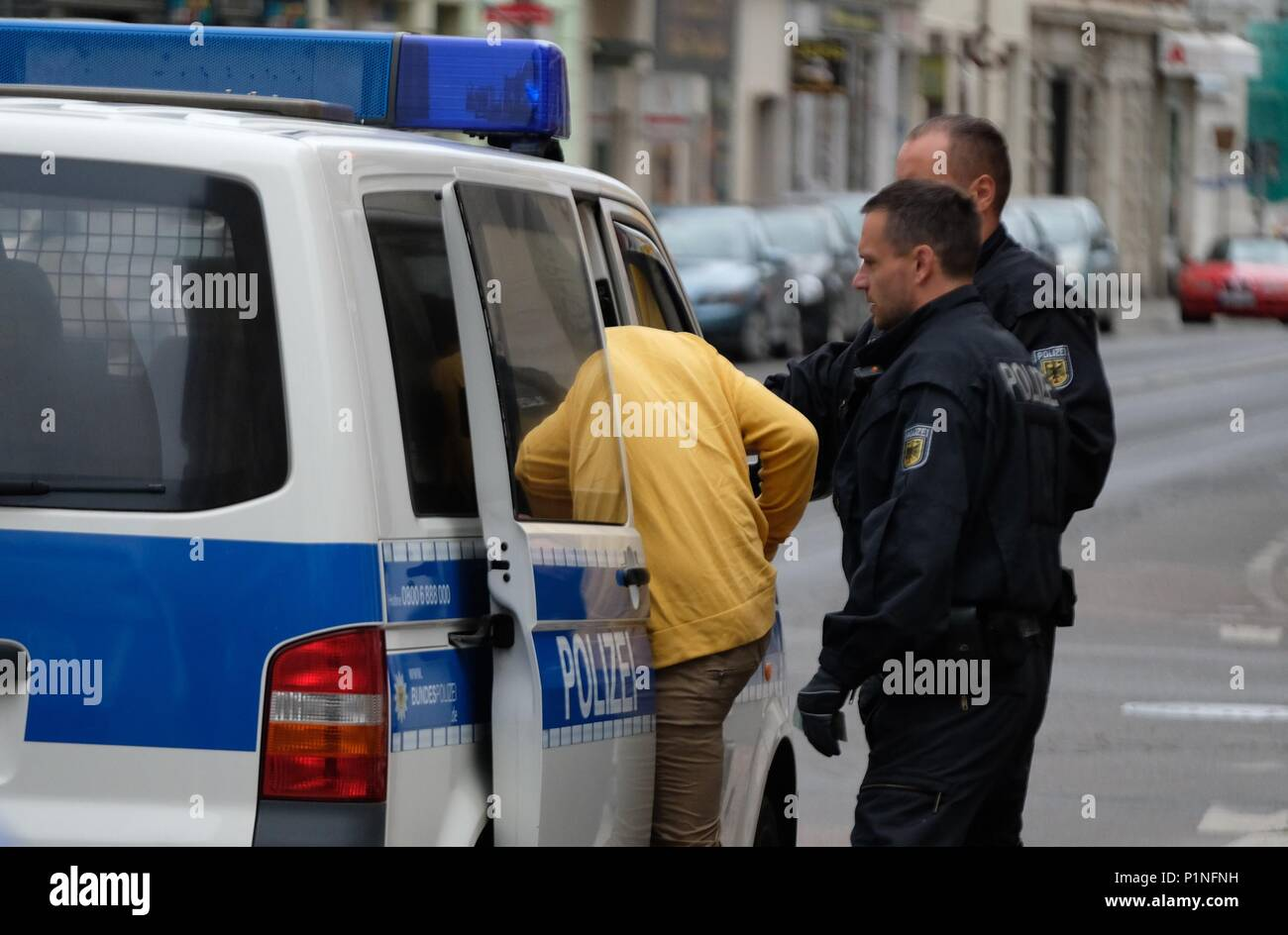 13 June 2018, Leipzig, Germany: Officers of the federal police accompany a man to a police vehicle. A police deployment took place due to  sham marriage suspicions. Photo: Sebastian Willnow/dpa-Zentralbild/dpa - Stock Image