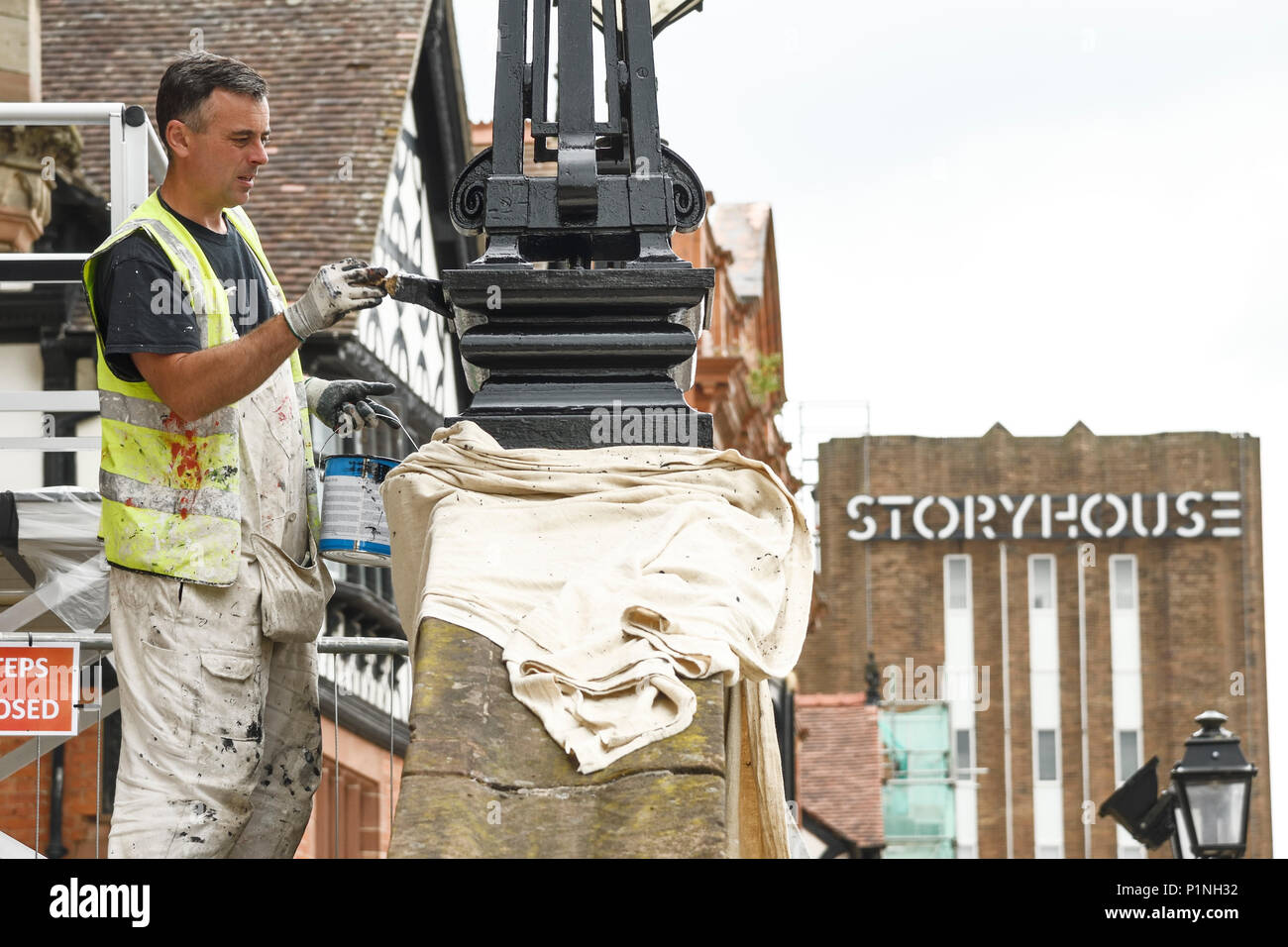 Chester, UK. 13th June 2018. A painter puts finishing touches to street furniture outside the Town Hall. Tomorrow the Queen and the Duchess of Sussex Meghan Markle will visit the city to officially open the Storyhouse theatre, library and arts venue before having lunch in the Town Hall. Credit: Andrew Paterson/Alamy Live News - Stock Image