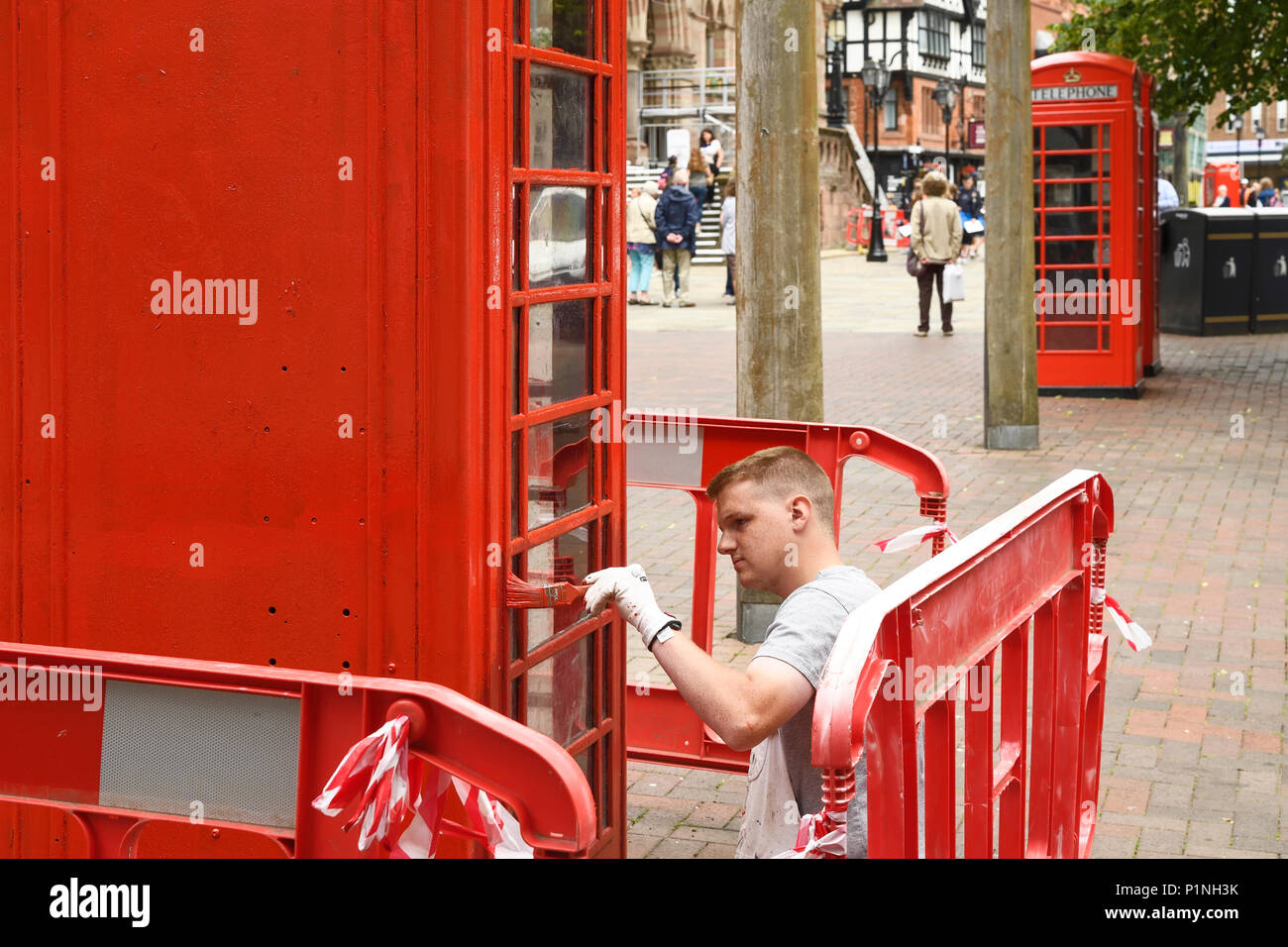 Chester, UK. 13th June 2018. A painter puts finishing touches to a red phone box outside the Town Hall. Tomorrow the Queen and the Duchess of Sussex Meghan Markle will visit the city to officially open the Storyhouse theatre, library and arts venue before having lunch in the Town Hall. Credit: Andrew Paterson/Alamy Live News - Stock Image