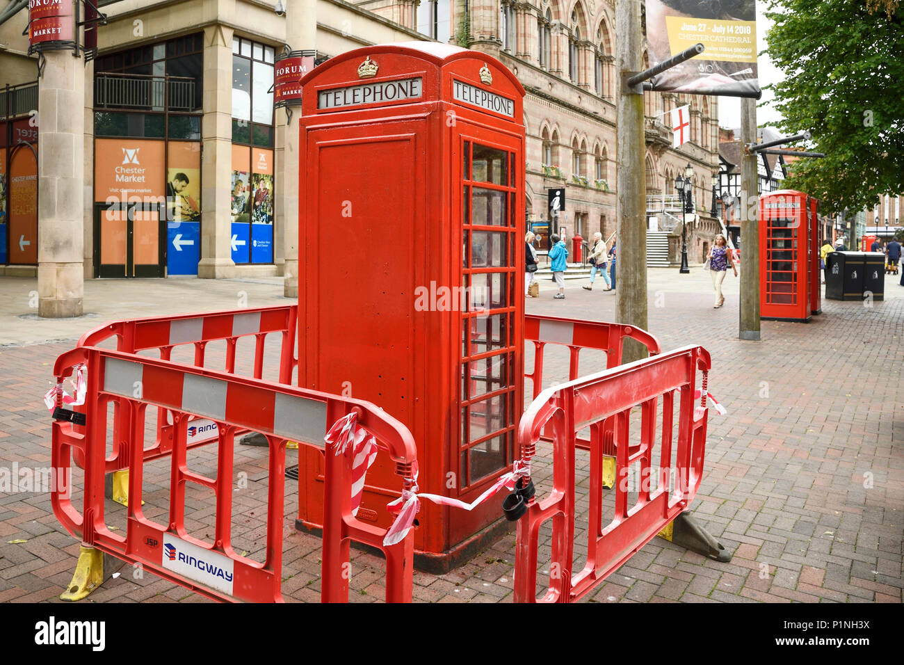 Chester, UK. 13th June 2018. A red phone box outside the Town Hall is given a fresh coat of paint. Tomorrow the Queen and the Duchess of Sussex Meghan Markle will visit the city to officially open the Storyhouse theatre, library and arts venue before having lunch in the Town Hall. Credit: Andrew Paterson/Alamy Live News - Stock Image