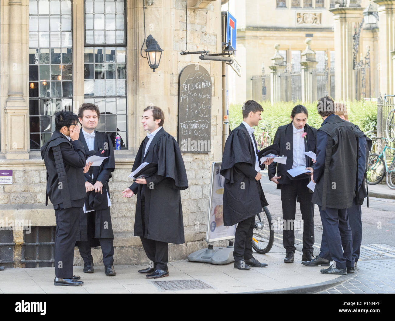 Students (with pink carnations) in deep discussion outside a pub at the corner of High Street and Merton Lane after an exam at university of Oxford. - Stock Image