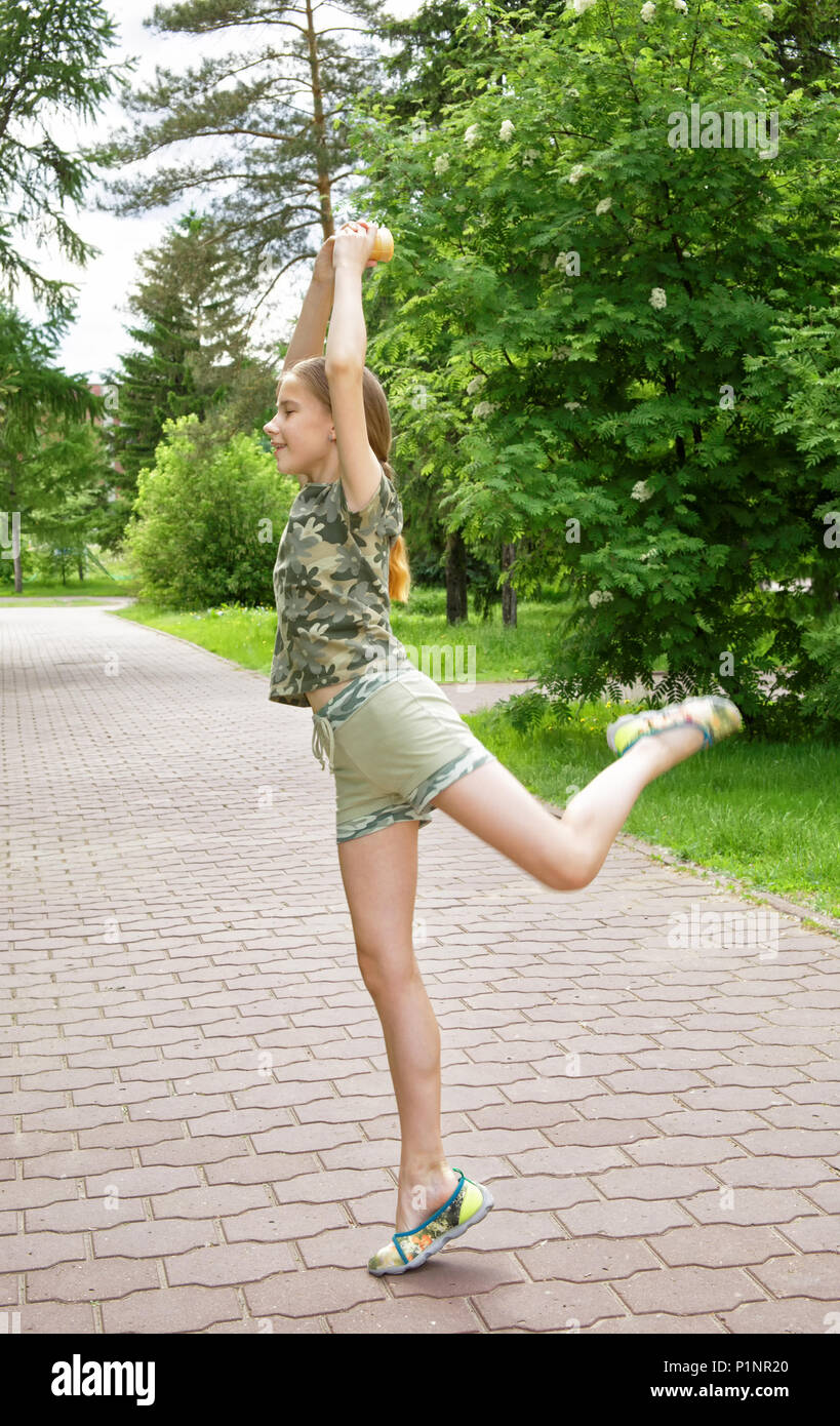 Slender Teen Girl With Ice Cream In Hand Dancing In The Park Enjoying The Coming Vacation Choreographic Exercises On The Alley Among The Trees