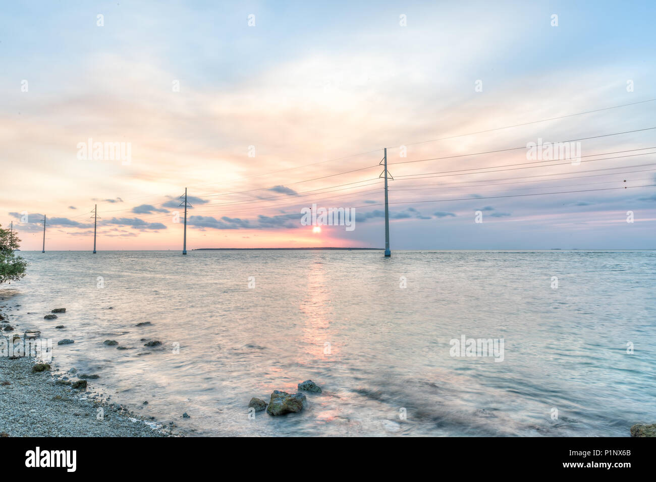 Sunset in Islamorada, Florida Keys, with pink sky, rocks, power lines, rocky beach, hdr green shallow water on gulf of Mexico, or Atlantic Ocean, hori Stock Photo