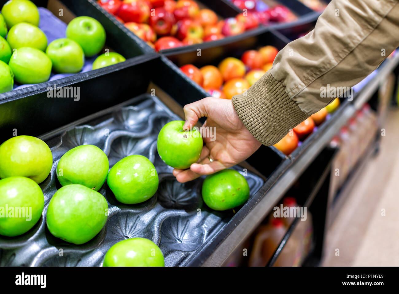 Green assorted apples on display shelf in grocery store boxes in aisle, supermarket inside, man person customer touching with hand holding granny smit - Stock Image