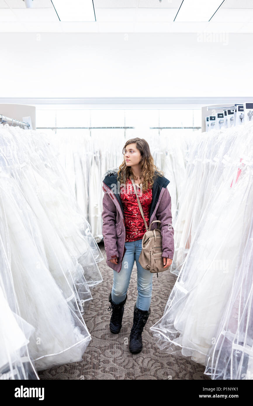 Young woman shopping for wedding dress gowns in boutique discount store aisle, many white garments hanging on rack hangers row - Stock Image
