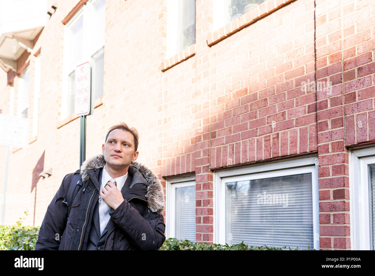 Young serious businessman face standing in front of brick wall, fixing tie, in suit and tie on interview break outside - Stock Image