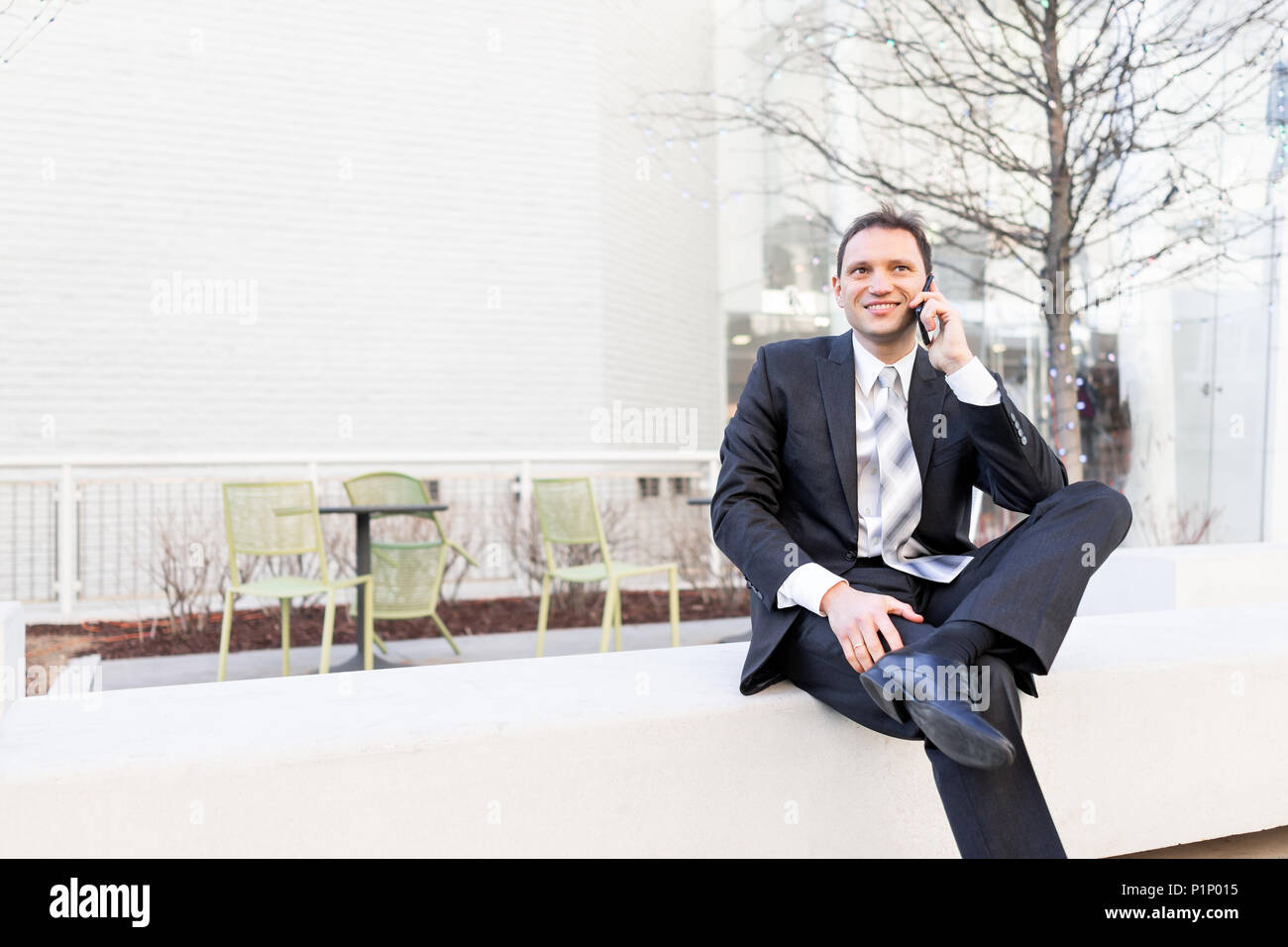 Handsome, attractive young businessman smiling sitting on bench in park, using talking holding smartphone phone mobile cellphone smiling in suit and t - Stock Image