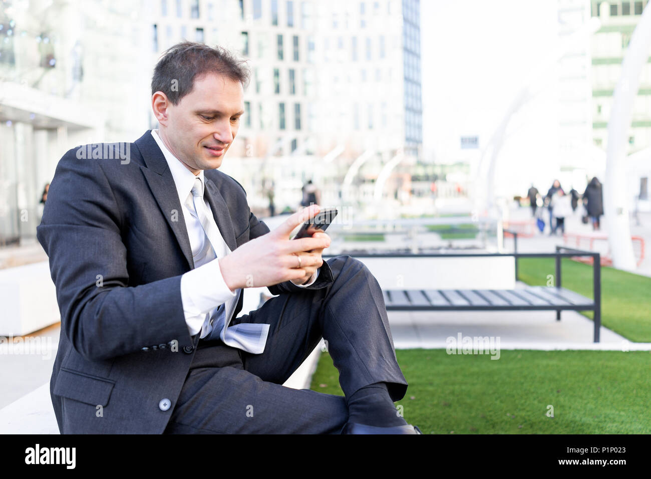 Young businessman smiling sitting on bench in park, using holding smartphone phone mobile cellphone smiling looking down texting in suit and tie, chee - Stock Image