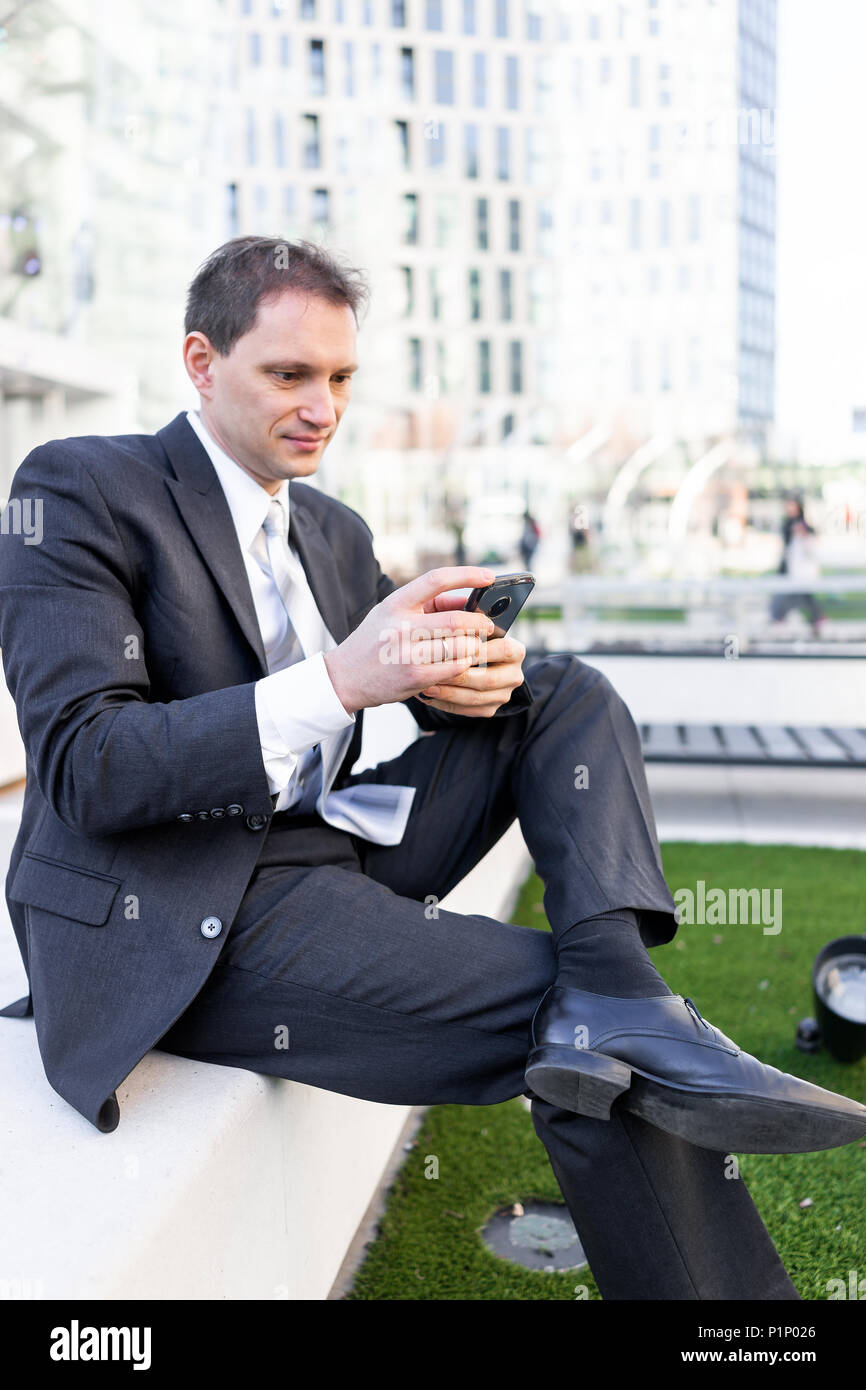 Young businessman sitting on bench in park, using smartphone phone mobile cellphone smiling looking down texting in suit and tie, cheerful on intervie - Stock Image