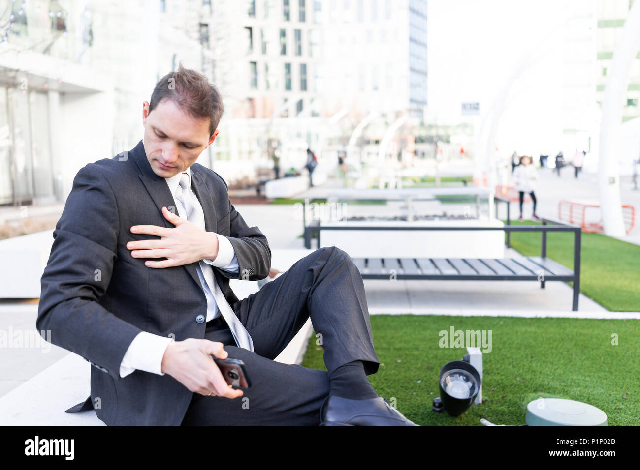 Young businessman cleaning dusting off suit sitting on bench in urban green park looking down with tie on interview break - Stock Image