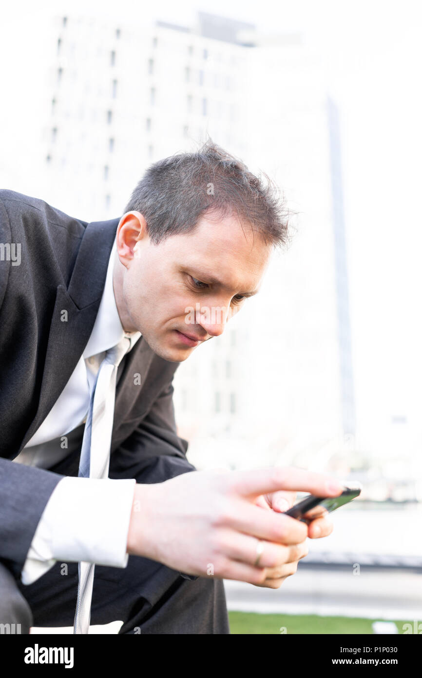 Young businessman sitting on bench in park closeup of face, using smartphone phone mobile cellphone smiling looking down texting in suit and tie on in - Stock Image