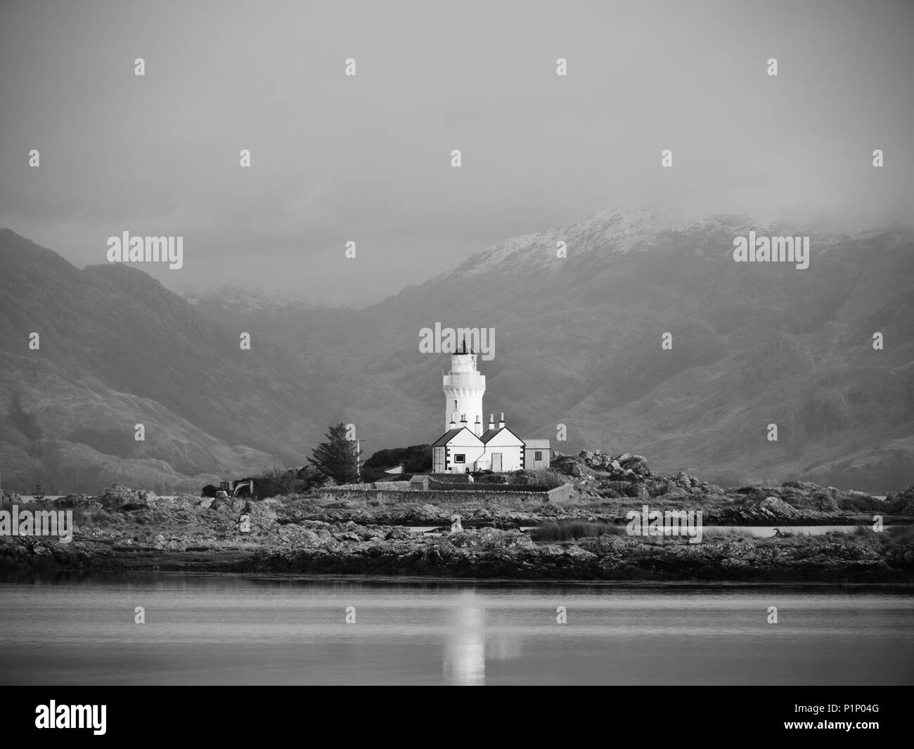 Iasle Ornsay Lighthouse built on a small islet  located on the ferry route. Low level of smooth water. Snowy mountain peaks hidden in cloudy backgroun - Stock Image