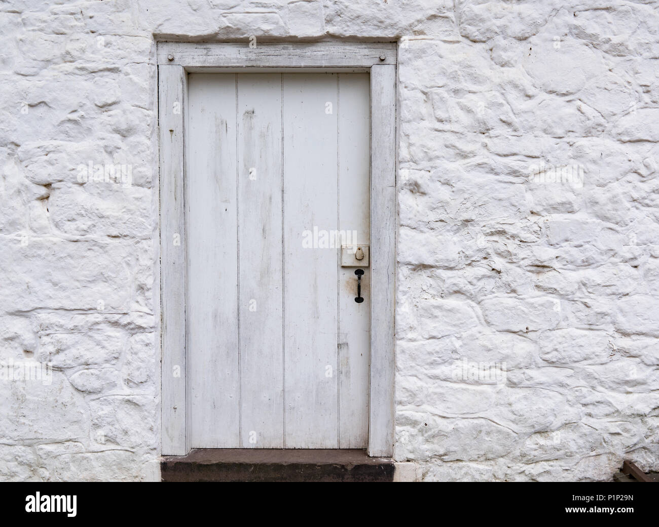 Old White weathered wooden door on a whitewashed stone building