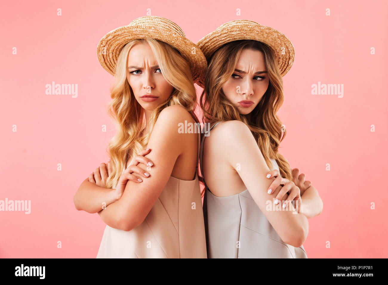 Portrait of two upset young women in summer clothes standing back to back and looking at camera isolated over pink background Stock Photo