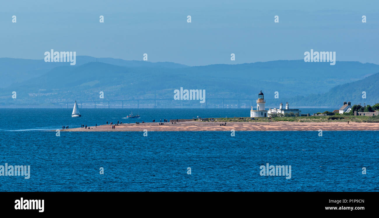 CHANONRY POINT MORAY FIRTH SCOTLAND WITH LIGHTHOUSE PEOPLE ON THE BEACH AND KESSOCK BRIDGE INVERNESS IN DISTANCE - Stock Image