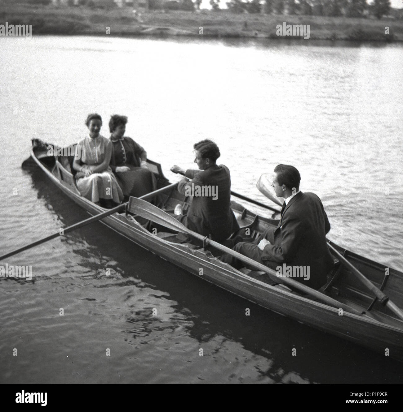 1955, historical, courting?..... two well-dressed young adult couples on the River Thames in a rowning boat at Teddington, Surrey, England, UK. - Stock Image