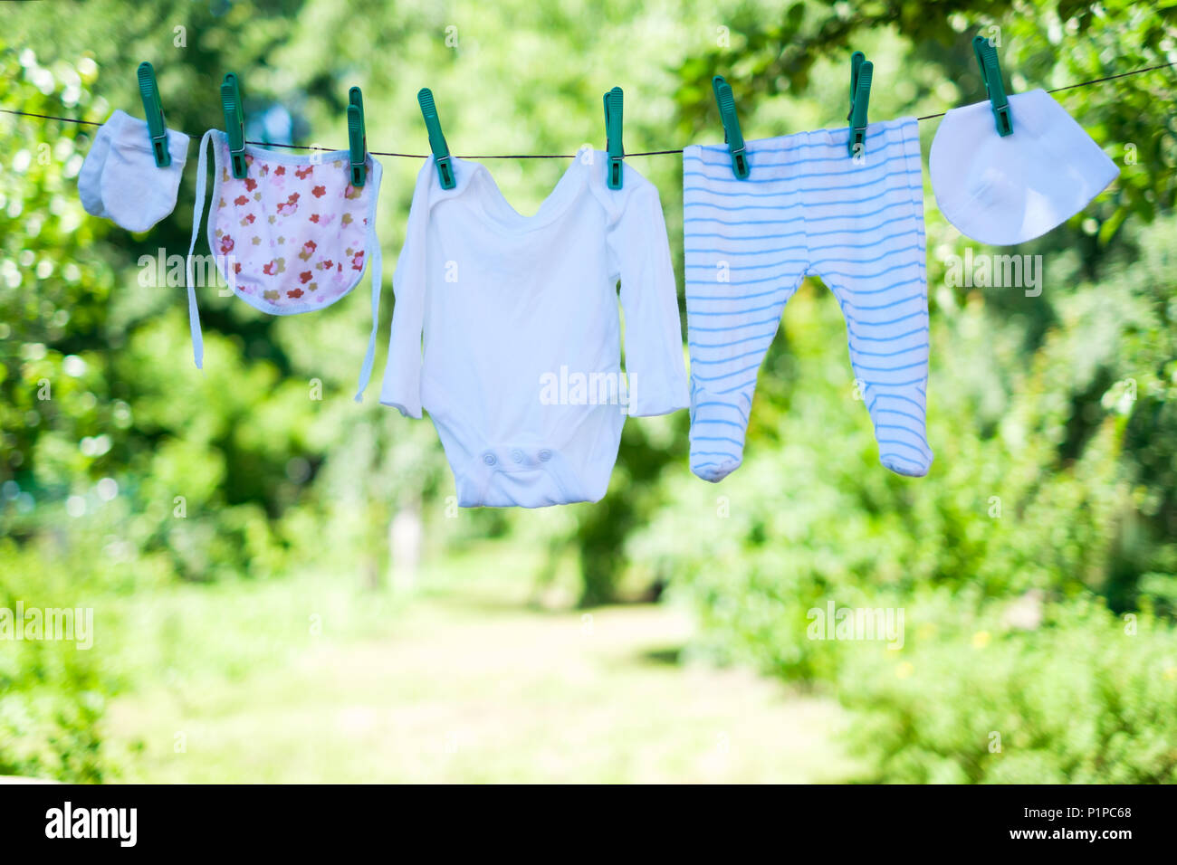 Baby clothes on clothesline in garden - Stock Image