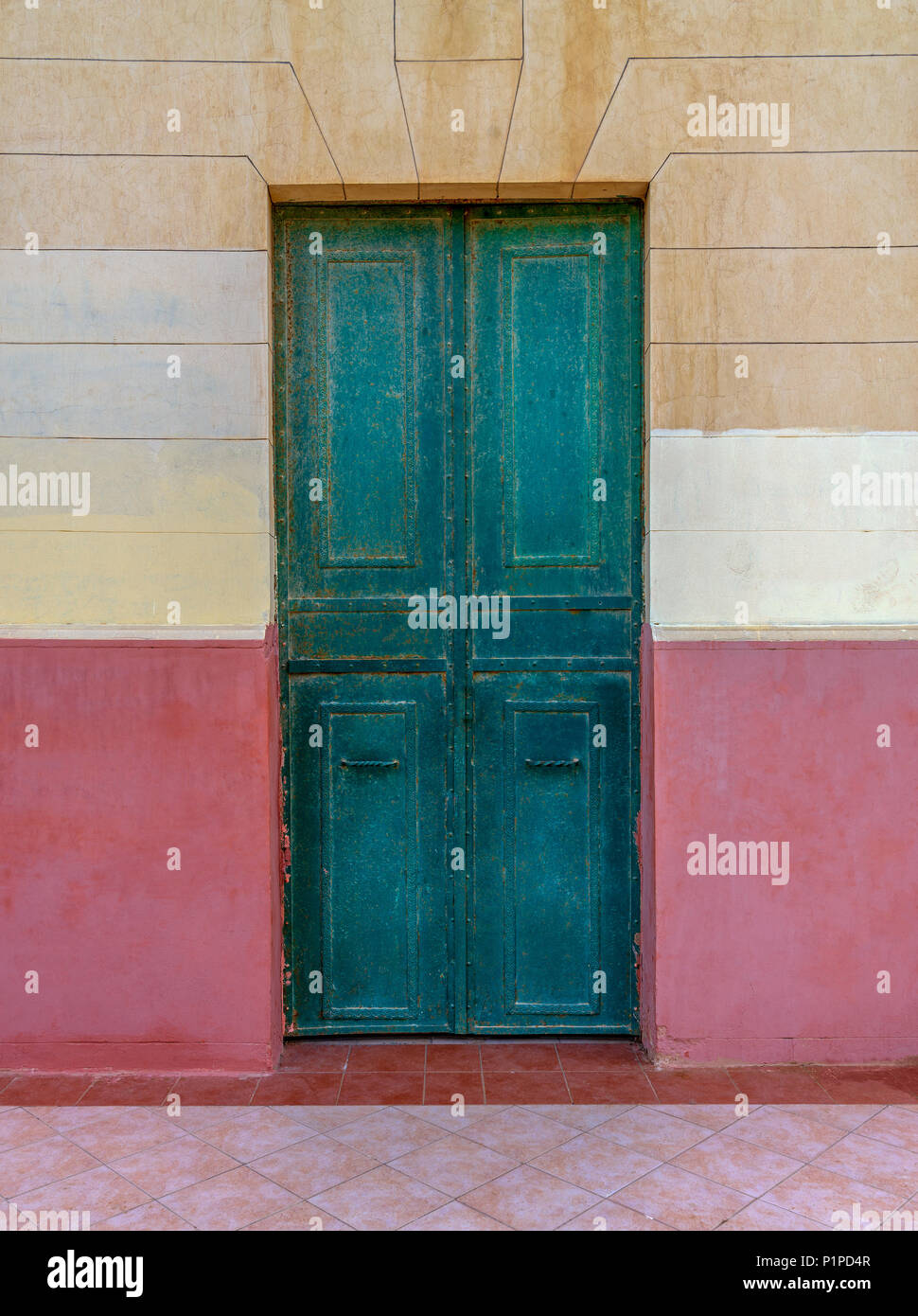 Old grunge green wooden door in an old wall painted in beige and red, Montaza Public Park, Alexandria, Egypt - Stock Image