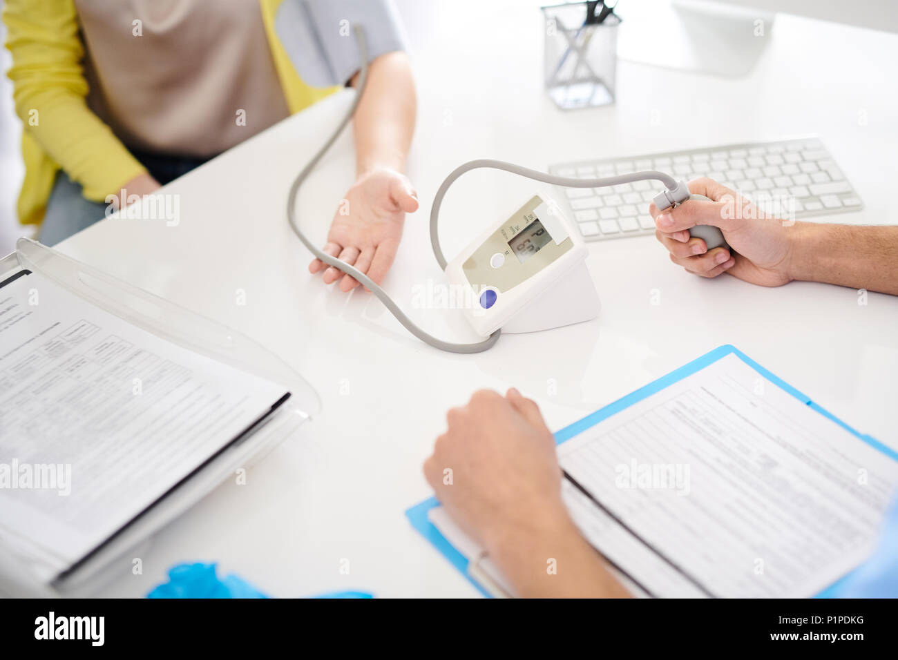Doctor Using Electronic Blood Pressure Monitor - Stock Image