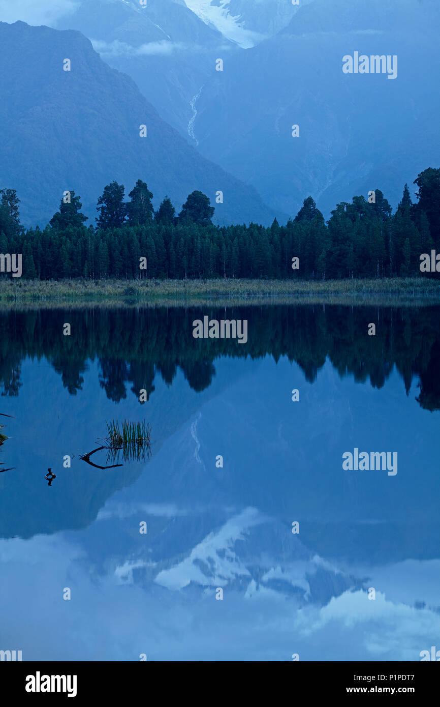 Reflection of Southern Alps in Lake Matheson, Westland National Park, West Coast, South Island, New Zealand - Stock Image