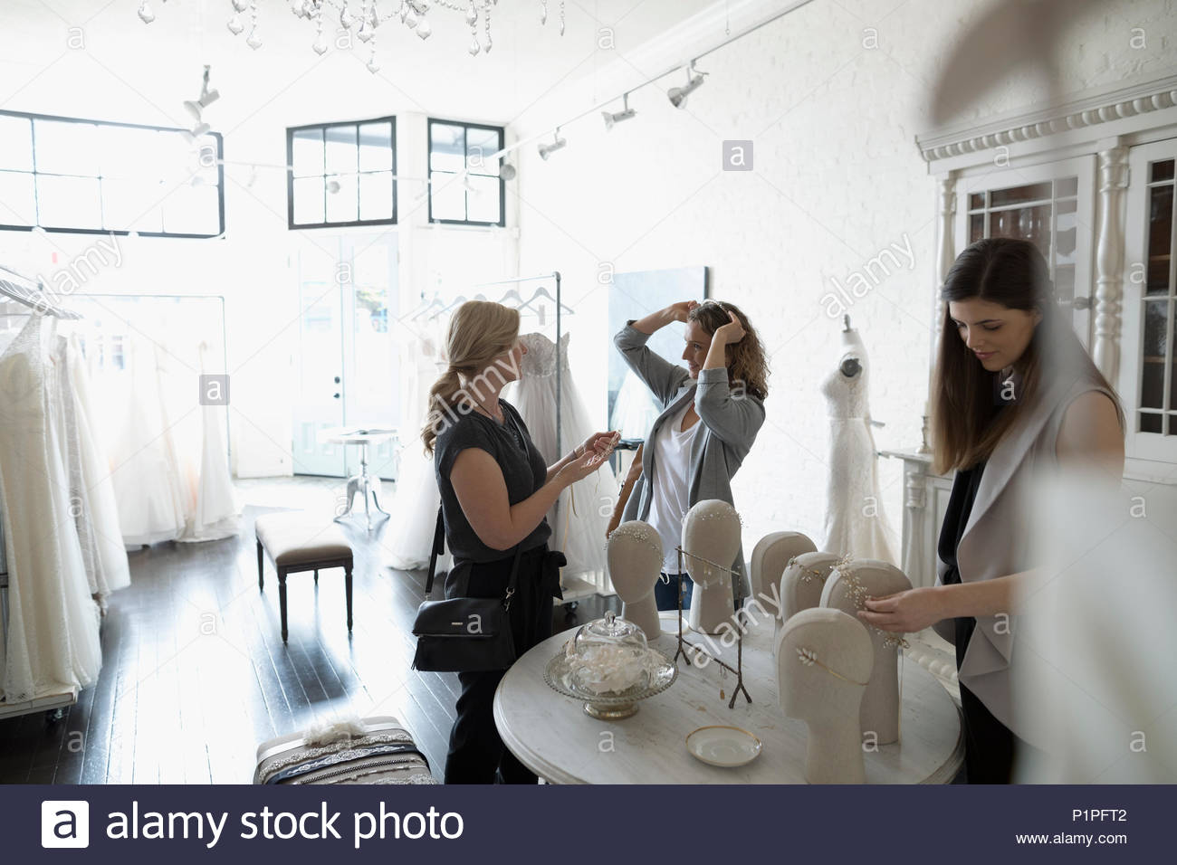 Bride trying on headbands at bridal boutique - Stock Image