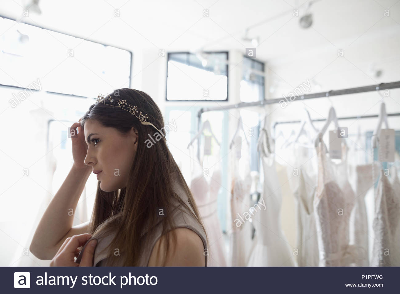 Bride trying on headband at bridal boutique - Stock Image