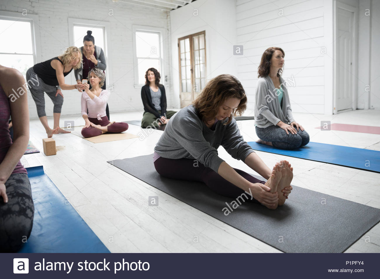 Woman practicing yoga forward bend in yoga class - Stock Image