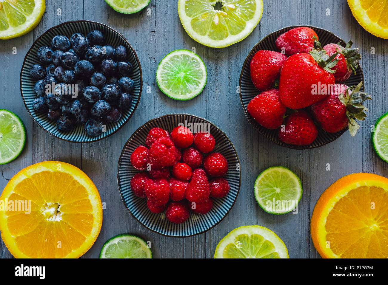 Strawberries, Raspberries and Blueberries with Oranges, Limes and Lemons on Blue Table - Stock Image