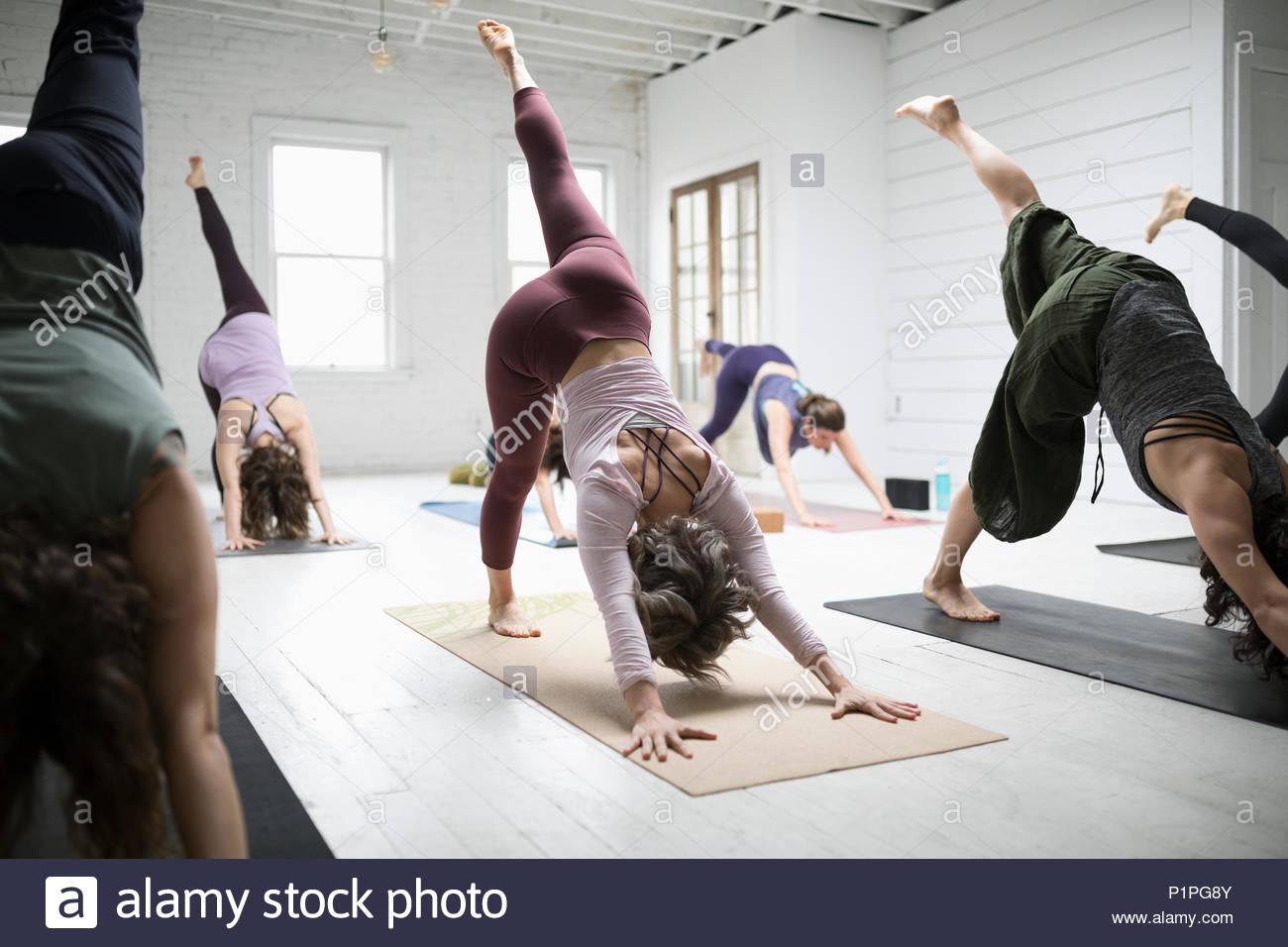 Women practicing yoga three legged dog pose - Stock Image