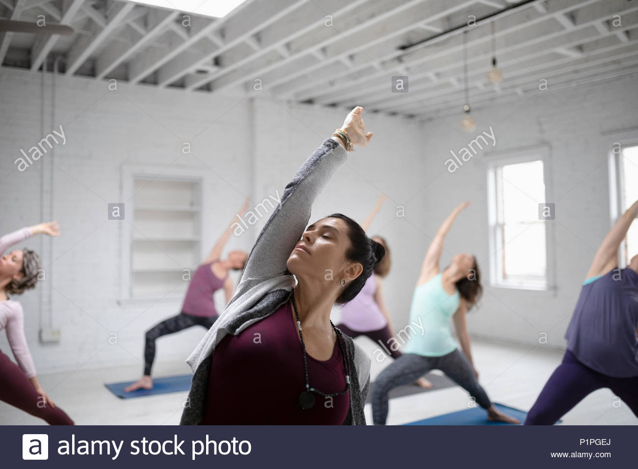 Focused woman practicing yoga reverse warrior pose in yoga class - Stock Image