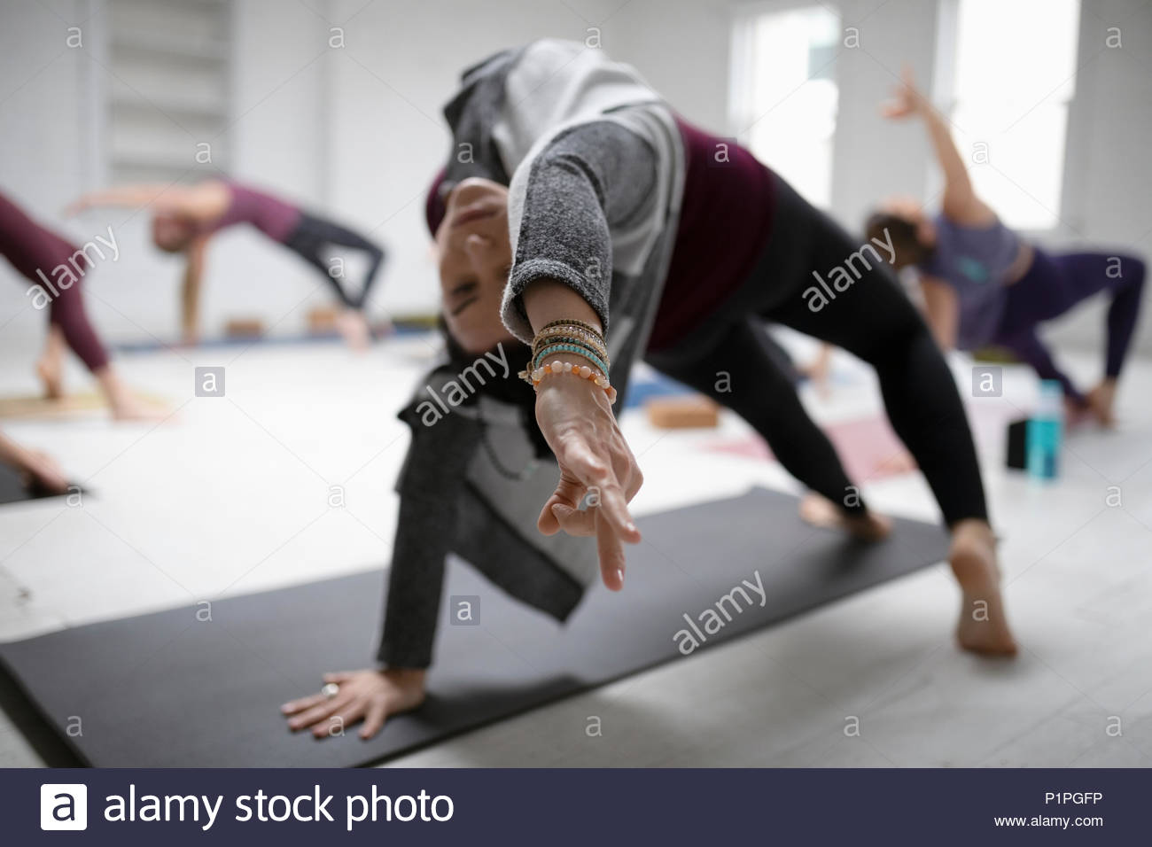 Woman practicing yoga backbend pose and gyan mudra in yoga class - Stock Image