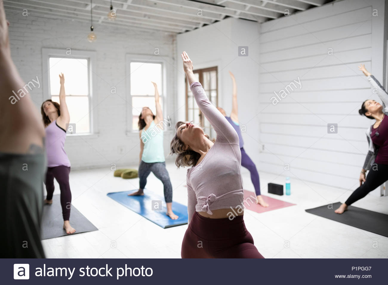 Women practicing yoga reverse warrior pose in yoga class - Stock Image