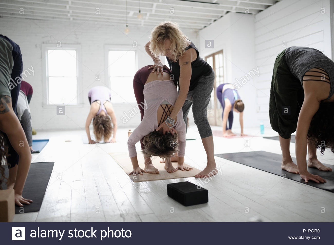 Yoga instructor helping woman practicing forward bend in yoga class - Stock Image