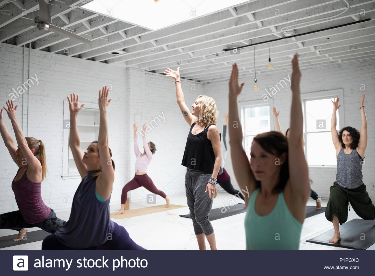 Yoga instructor guiding women practicing warrior one pose in yoga class - Stock Image