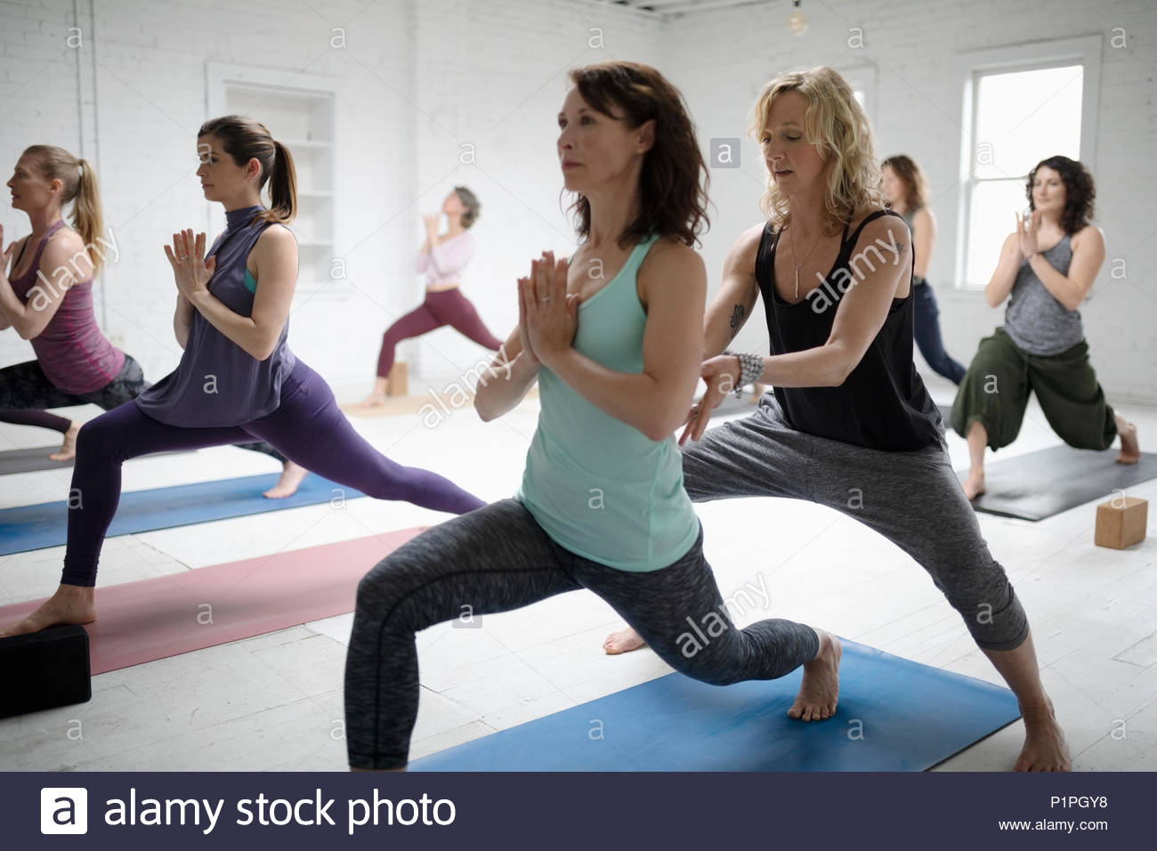 Yoga instructor guiding woman practicing warrior one pose - Stock Image