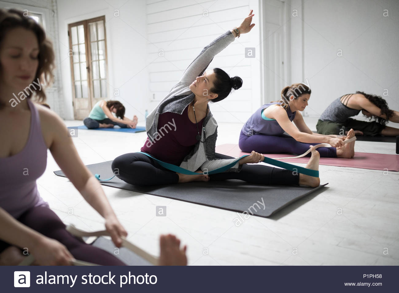 Woman practicing yoga side bend stretch with strap in yoga class - Stock Image