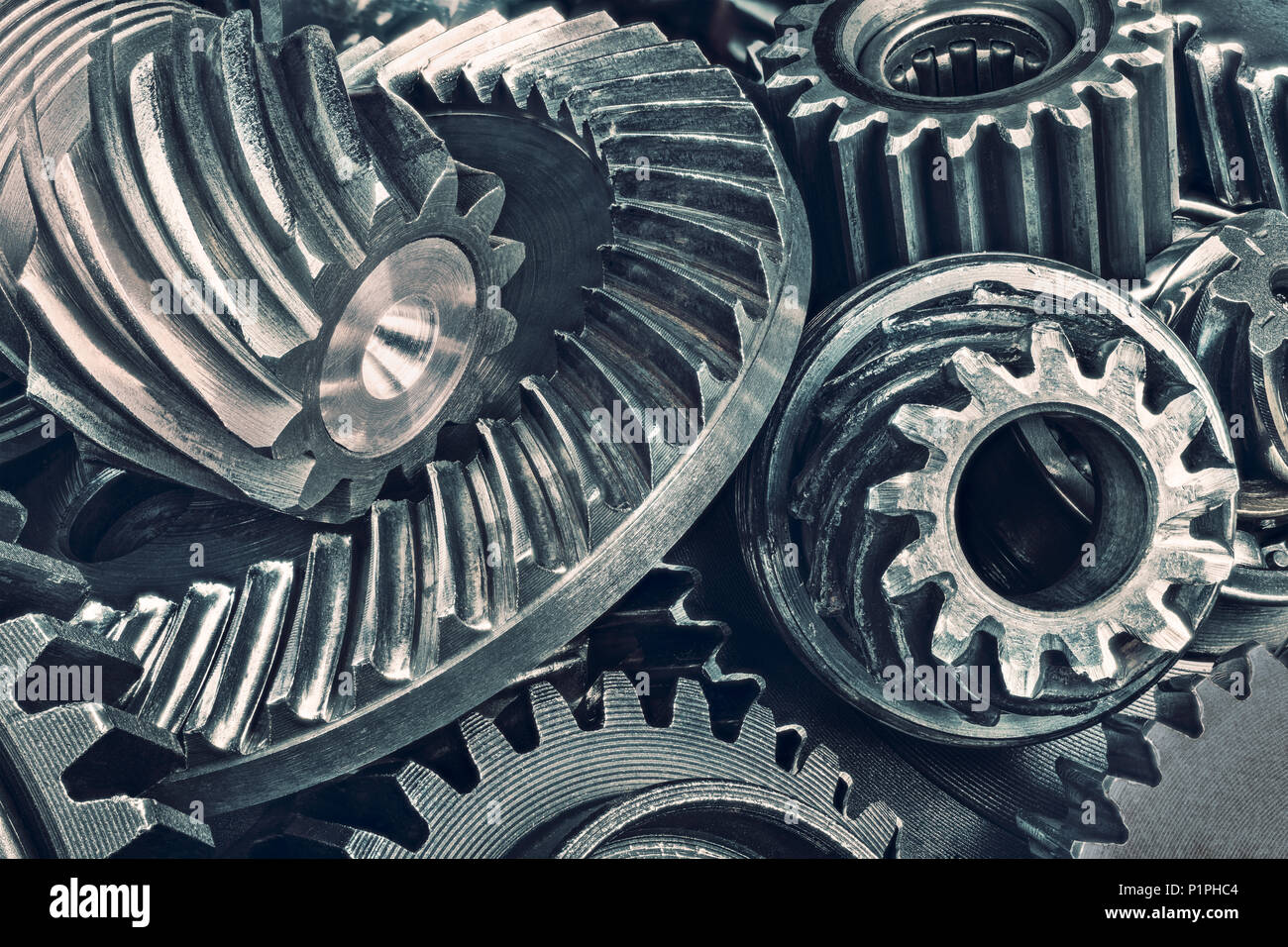 Close-up of various steel gear wheels. Cogged parts in duplex toning. Abstract technical background from the pile of metallic cogwheels. Quality idea. - Stock Image