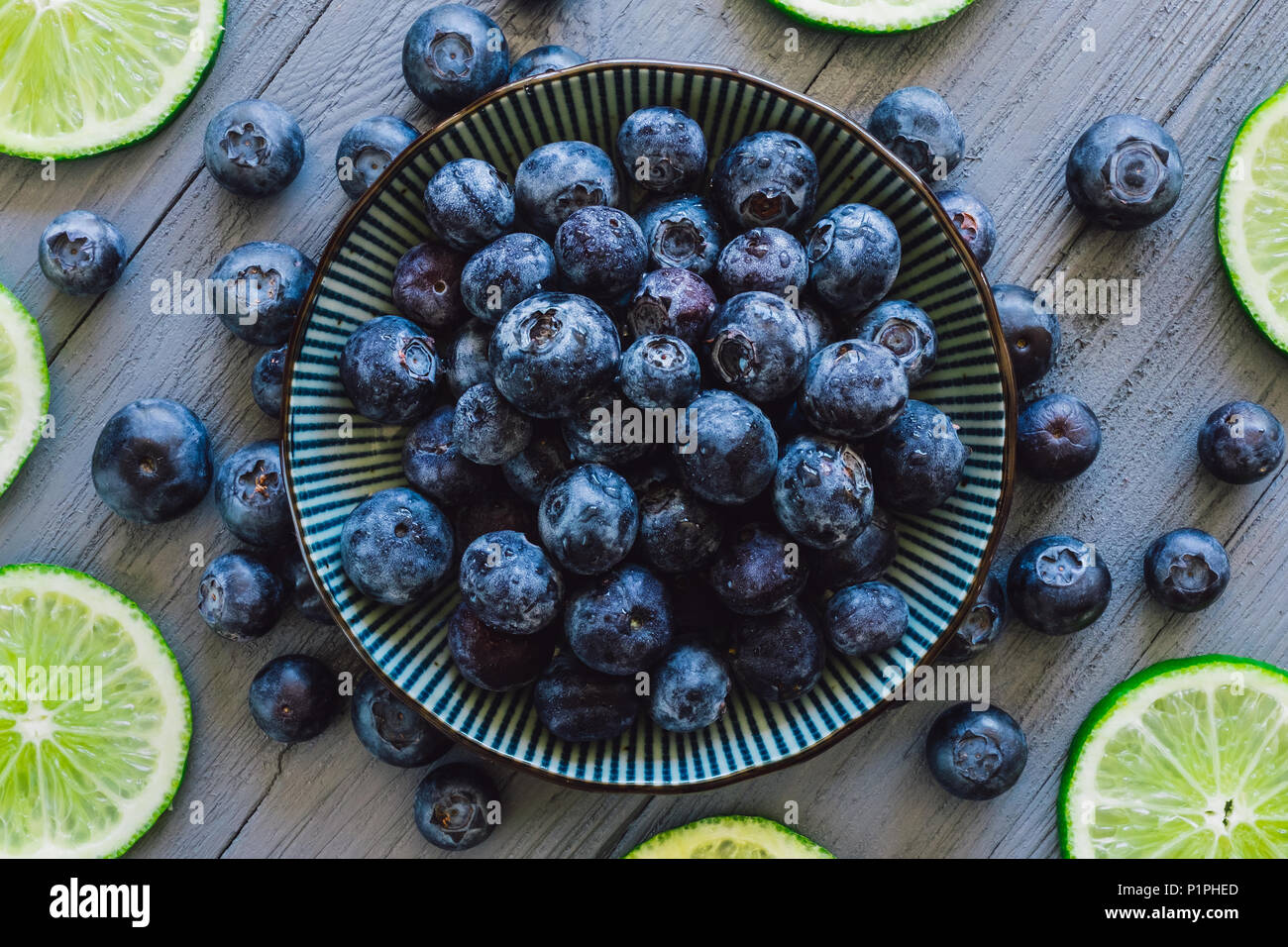 Centered Bowl of Blueberries with Scattered Berries and Sliced Limes on Blue Table - Stock Image