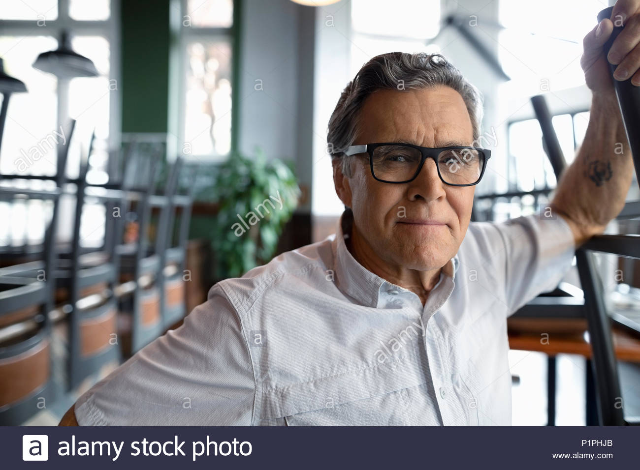 Portrait confident senior restaurant owner - Stock Image