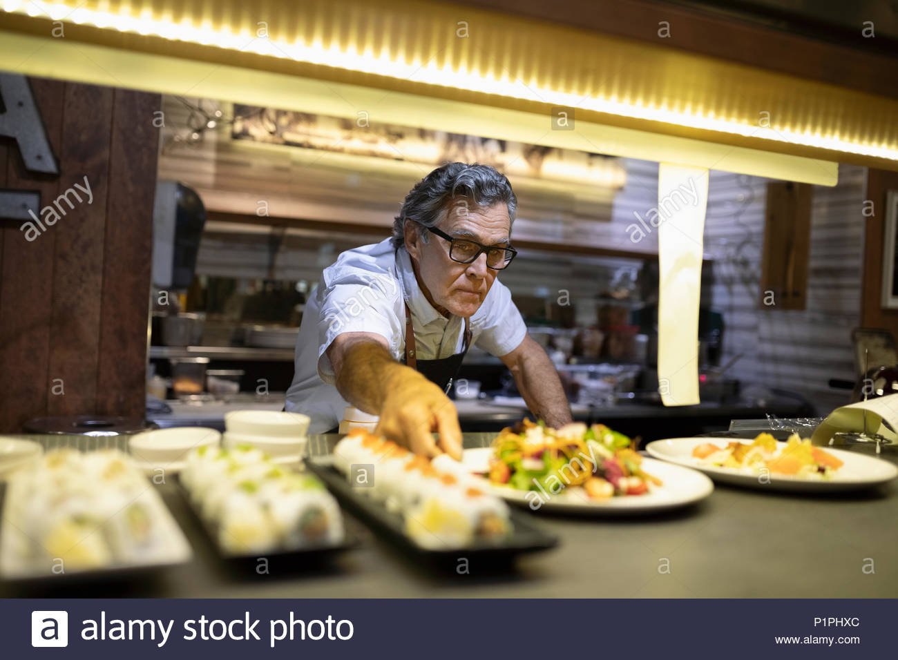 Senior chef plating food in restaurant kitchen - Stock Image