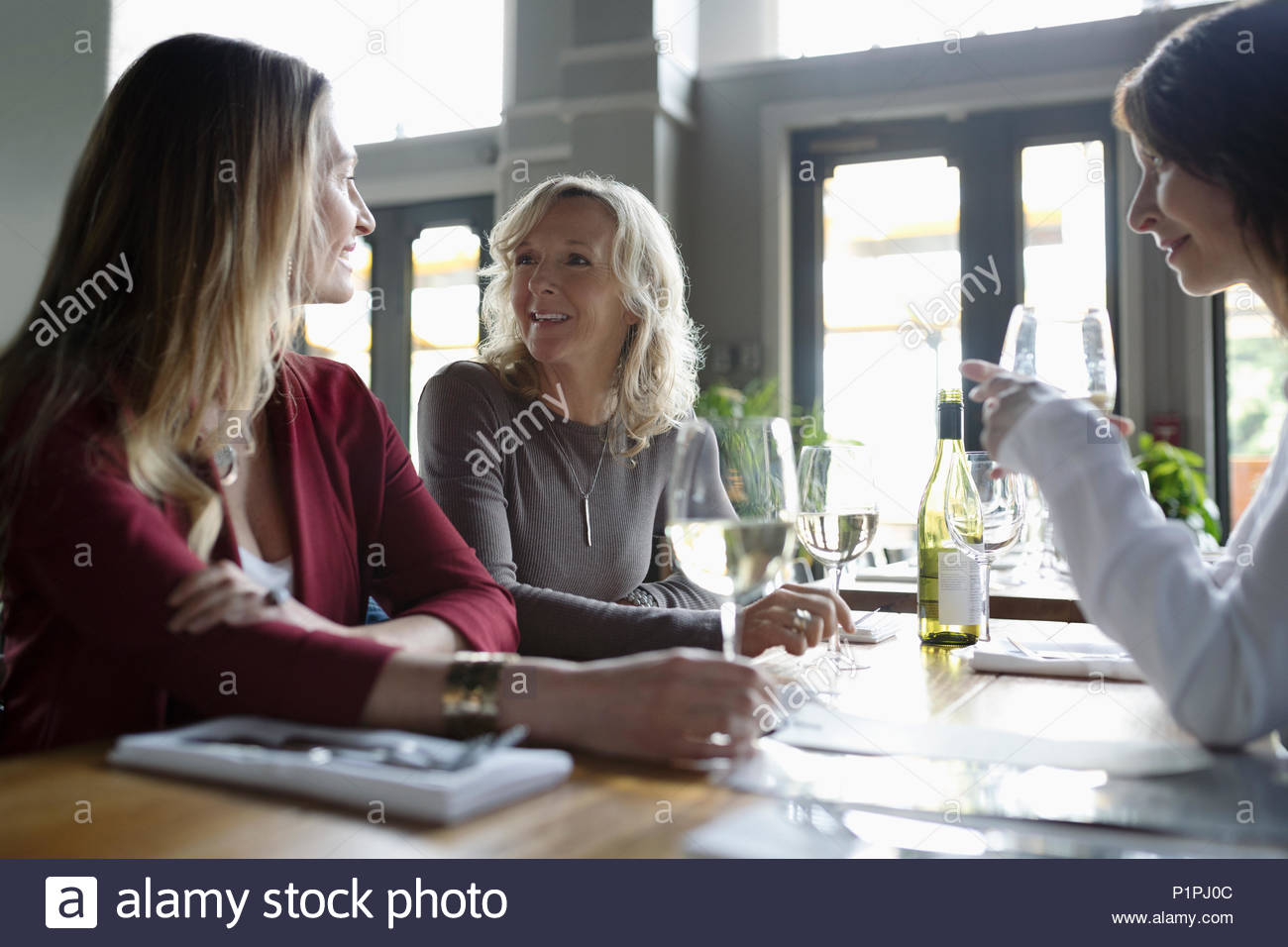 Women drinking wine, dining in restaurant Stock Photo