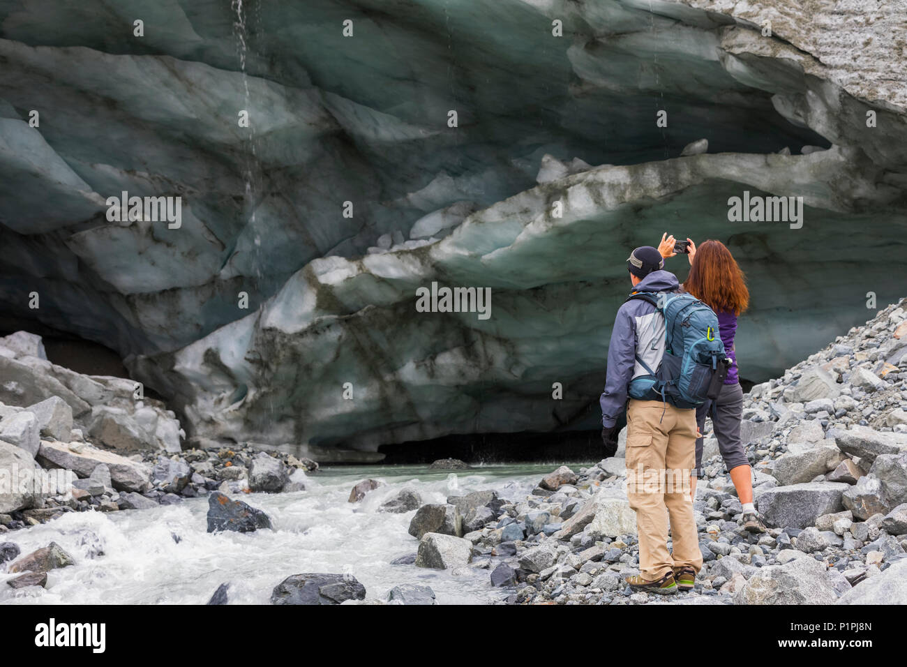 A woman takes a photograph of an ice cave with her cell phone while hiking to Gulkana Glacier with her husband; Alaska, United States of America - Stock Image