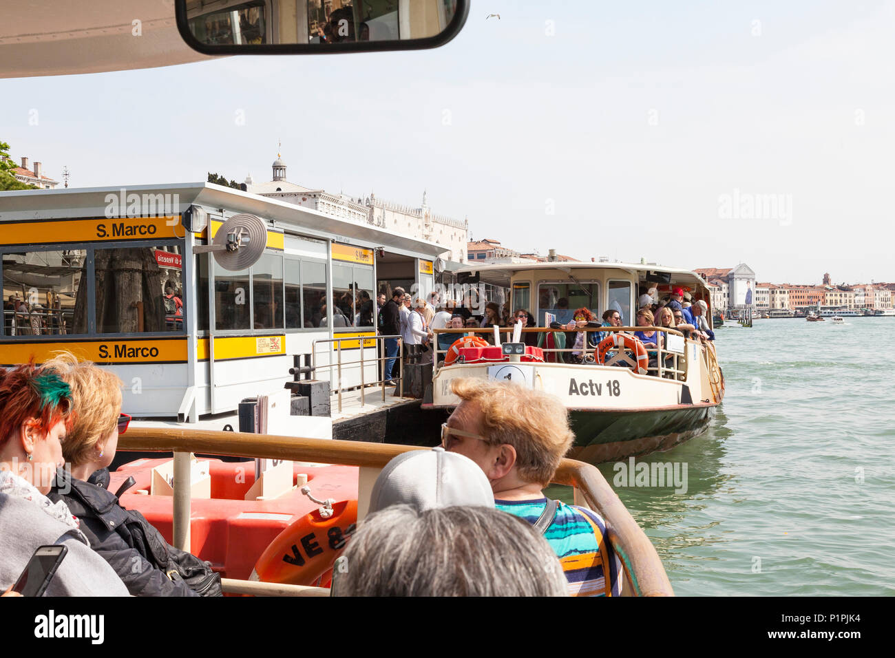 Travelling by overcrowded vaporetto waterbus in Venice, Veneto,  Italy with crowds of people boarding a boat at the San Marco stop in a first person P - Stock Image
