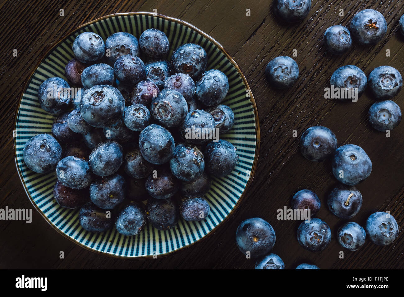 Bowl of Fresh Blueberries Arranged on Wood Table - Stock Image