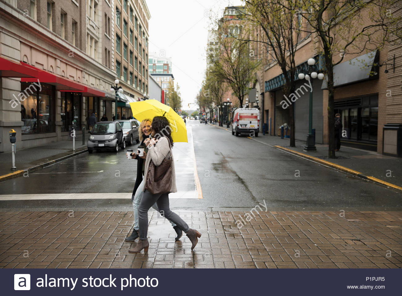 Women friends with yellow umbrella crossing city street - Stock Image