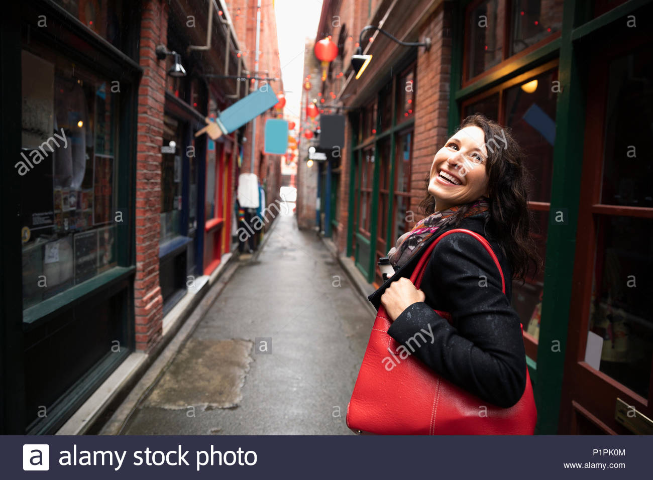 Smiling, carefree woman in urban alley - Stock Image