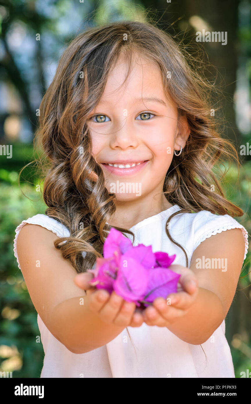 Portrait of a Caucasian five years old girl smiling and offering purple flowers in a park as a gift - Stock Image