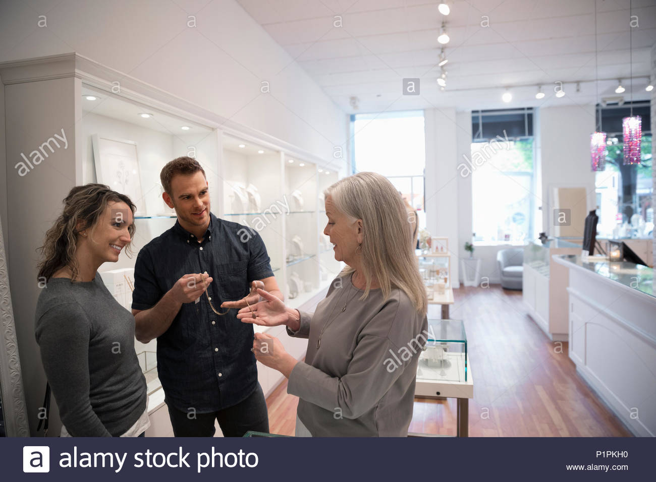 Jewelry boutique owner helping couple chopping for necklace - Stock Image
